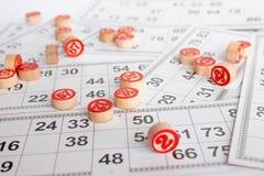 Bingo ou jogo do loto Barris de madeira do loto em cart?es Cart?es e microplaquetas para jogar o bingo em uma tabela branca foto de stock