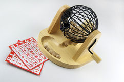 Bingo!. Wooden bingo numbers coming out of the shoot and resting in a row spelling B I N G O. Cards and bingo cage Royalty Free Stock Images