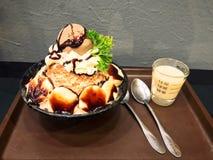 Bingsu do chocolate e da banana com cobertura tal como o gelado de chocolate, o creme wipping e o vegetal no copo cerâmico preto  imagens de stock royalty free