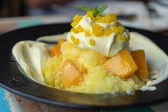 Bingsu mango dekoruje z serową polewą, słuzyć z słodzącym zgęszczonym mlekiem w czarnym talerzu Koreańczyka stylowy deserowy świe obraz stock