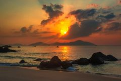 Nature Seascape with Tranquil Beach, Boulders, Islands and Bursting Sun at Sunrise royalty free stock images