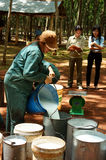 Worker weigh latex rubber at rubber plantation Royalty Free Stock Photos
