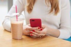 Binnen bebouwd beeld die van onherkenbare vrouw haar smartphone in beide handen houden, zittend bij lijst, die plastic kop hebben royalty-vrije stock afbeelding