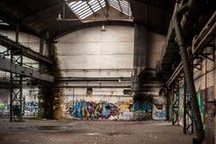 Binnen de oude en verlaten fabrieksbouw met graffiti royalty-vrije stock afbeeldingen