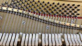 Binnen de piano: koord, spelden en hamers stock videobeelden