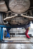 Binnen een garage - twee werktuigkundigen die aan een auto werken stock fotografie