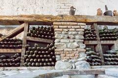 Binnen een wijnkelder met oude stofflessen en rustieke houten planken Historische opslag van wijnmakerij Royalty-vrije Stock Afbeelding