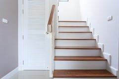Binnen eigentijds wit modern huis met houten trap stock foto