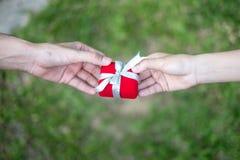 Binnen gevend rode giftdoos met handen op speciale dagen voor speciale persoon, op grasachtergrond Trouwringdoos royalty-vrije stock afbeelding