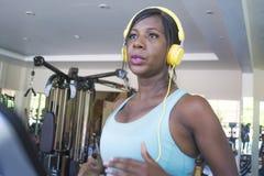 Binnen gymnastiekportret van jonge aantrekkelijke zwarte afro Amerikaanse vrouw die met hoofdtelefoons hard een harde tredmolen l royalty-vrije stock afbeeldingen