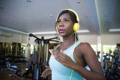 Binnen gymnastiekportret van jonge aantrekkelijke zwarte afro Amerikaanse vrouw die met hoofdtelefoons hard een harde tredmolen l royalty-vrije stock foto's