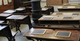 Binnen het oude uitstekende houten klaslokaal met brandplaats in het midden royalty-vrije stock foto's