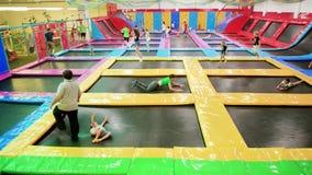 Binnen springend op trampolines in lokaal pretpark, de activiteiten van de familiesport, gezonde levensstijl stock footage