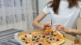 Binnen video die van de hand van het meisje een stuk van pizza met paddestoelen houden, kaas, maïs, olijven, rode uiringen en stock videobeelden