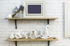 Binnenhuisarchitectuurspeelgoed Witte decoratieve vogel dichtbij kooi en ceramische paarden en fotokader in duur binnenland royalty-vrije stock fotografie