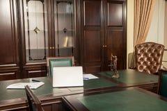 Binnenland van bureauruimte met laptop, beeldje en documenten stock afbeeldingen