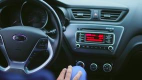 Binnenland van de auto Bestuurder die radiomontages schakelen en de muziek luisteren