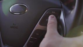 Binnenland van de auto De mens controleert de wijzen van muziek in auto op stuurwiel stock video