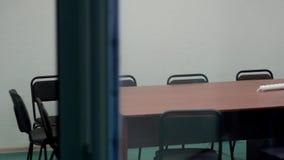 Binnenland van een bureau met houten groot bureau en vele zwarte stoelen stock video