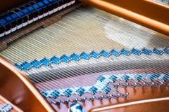 Binnenland van een grote piano, die koorden en hamers tonen stock foto