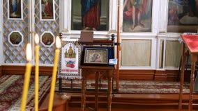 Binnenland van een kleine Oekraïense Orthodoxe kerk Kaarsen, pictogrammen en andere godsdienstige symbolen stock footage