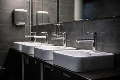 Binnenland van een modern openbaar badkamerstoilet in grijze kleuren stock foto