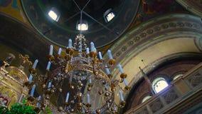 Binnenland van een oude de kroonluchterlamp van het kerkaltaar en een boog en kolom stock video