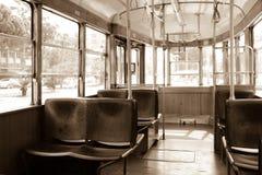Binnenland van een oude uitstekende tram Binnen is lege, houten zetels schaduwen Door de glasvensters kunt u de bomen zien Sepia Stock Foto