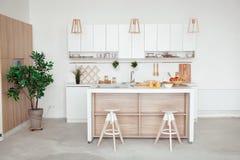 Binnenland van kleine witte keuken met vers fruit, twee glazen jus d'orange, baguette, rode kaviaar, croissant en Stock Foto's