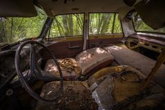 Binnenland van vergeten auto die in de tuin rotten stock afbeelding