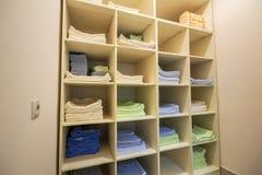 Binnenland van witte plastic kabinet of kledings open garderobe met gestapelde stapels van schoon kleurrijk linnen op planken meu stock foto's