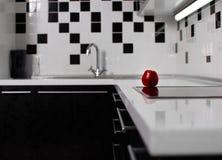 Binnenland van zwart-witte keuken met rode appel Stock Afbeeldingen