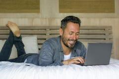 Binnenlands ontspannen portret van de jonge aantrekkelijke en gelukkige mens die thuis aan bed met laptop computer vrolijk binnen royalty-vrije stock afbeeldingen
