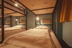 Binnenlands ontwerp van een dormruimte van toeristenherberg met schone bedden voor twaalf mensen stock afbeeldingen
