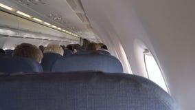 Binnenlands passagiersvliegtuig met mensen op zetels stock footage
