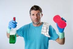 Binnenlandse de dienstmens of het vermoeide echtgenoot boze en beklemtoonde huis schoonmaken met nevelfles en spons Stock Fotografie
