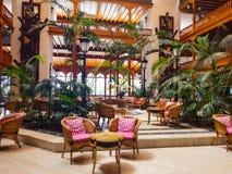 Binnenlandse die ontvangst van een hotel met edel hout in koloniale stijl en tropische vegetatie wordt verfraaid stock foto's