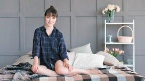 Binnenlandse jonge mooie vrouw in overhemdszitting op bed thuis binnenlands volledig schot stock videobeelden