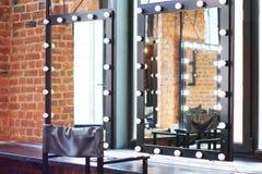 Binnenlandse kleedkamer met een stoel, een lijst, een spiegel en een licht in een fotostudio stock fotografie