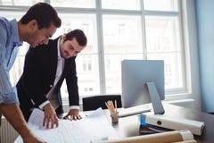 Binnenlandse ontwerper die blauwdruk bespreken met collega royalty-vrije stock afbeeldingen