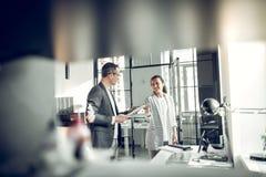 Binnenlandse ontwerper en zijn secretaresse die nieuw project bespreken stock fotografie