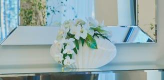 Binnenlandse ruimte, een vaas van bloemen en een decoratieve grote spiegel op een lichte muur stock fotografie