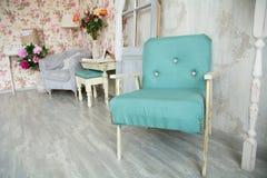 Binnenlandse ruimte met groene leunstoel, hoofdkussens, deur en bloemen Royalty-vrije Stock Afbeeldingen
