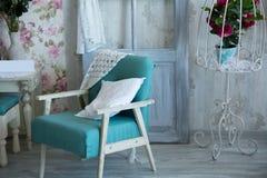 Binnenlandse ruimte met stoelen, hoofdkussens, deur en bloemen Royalty-vrije Stock Fotografie