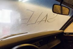 Binnenmening van oud gebroken autobinnenland met stoffig voertuigdashboard, achterspiegel, drijfstuurwiel en vuile wind royalty-vrije stock foto