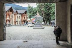 Binnenplaats van de toeristenstad van Mestia in het Svaneti-gebied met een koe in de boog en een beeldhouwwerk van Zwaan op een p stock foto