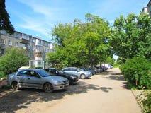Binnenplaats van de weg, de auto's, de bomen, en de huizen in de stad Stock Fotografie