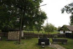 Binnenplaats van een traditioneel huis met fontein, omheining en gestapeld hout stock foto