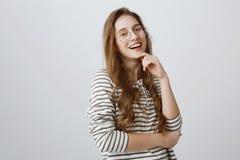 Binnenportret die van verbaasde knappe vrouwelijke student in transparante glazen status helft-gedraaid, hand houden op kin royalty-vrije stock foto's