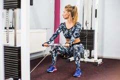 Binnenportret mooi sexy meisje in sportkleding in gymnastiek Stock Afbeeldingen